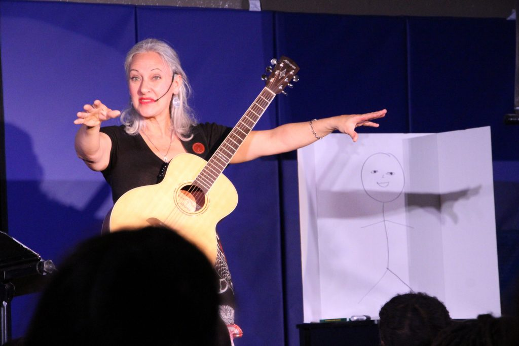 Hélène Nicole on stage, wearing a black shirt and colorful red white black skirt. Arms spread high to make children sing, she has a guitar. A stick man drawing on the white board.